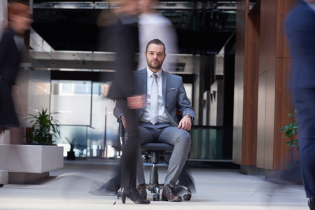 handsome young man: business man sitting in office chair,  people group  passing by: Concept of time, rush, organization