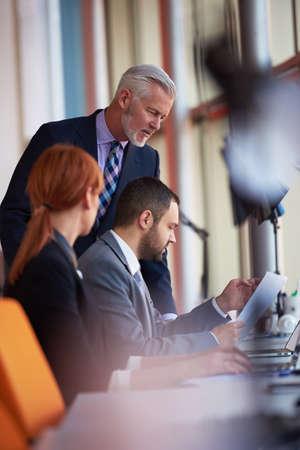 ejecutivo en oficina: grupo de personas de negocios con los adultos jóvenes y de alto nivel sobre la reunión en la oficina moderna interior brillante.