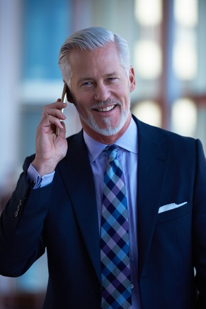 white suit: senior business man talk on mobile phone  at modern bright office interior Stock Photo