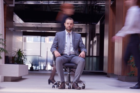 man in chair: business man sitting in office chair,  people group  passing by: Concept of time, rush, organization