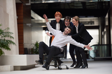 modern office: business people group at modern office indoors have fun and push office chair on corridor