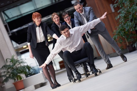 push people: business people group at modern office indoors have fun and push office chair on corridor