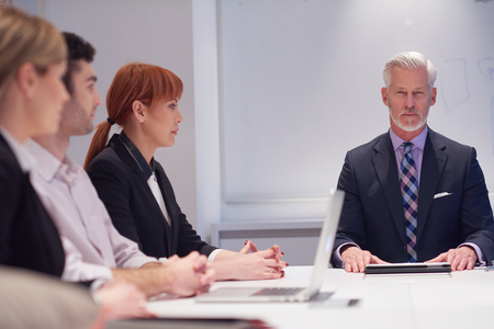 senior adults: business people group with young adults and senior on meeting at modern bright office interior. Stock Photo