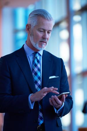 hablando por telefono: altos hombre de negocios habla por teléfono móvil en interior moderno oficina brillante Foto de archivo