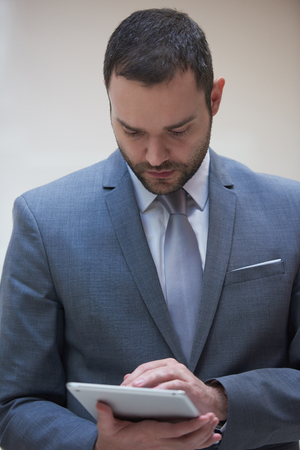 gray suit: portrait of young business man with tablet computer at modern office