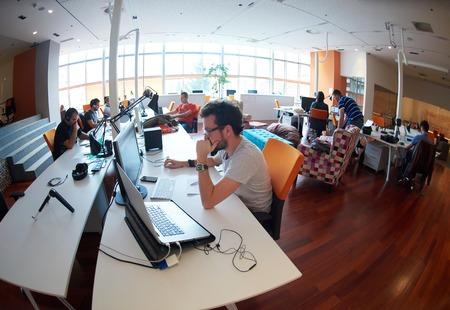 люди: запуск группы деловых людей, работающих повседневную работу в современном офисе