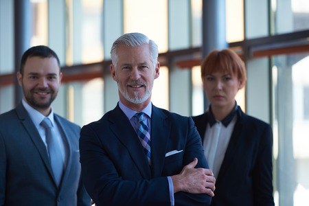 group of business people: senior businessman with his team at office. business people group