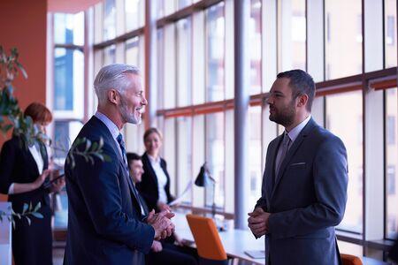 hombres trabajando: grupo de personas de negocios con los adultos jóvenes y de alto nivel sobre la reunión en la oficina moderna interior brillante.