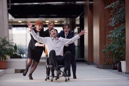 近代的なオフィスでビジネス人々 のグループは屋内で楽しい時を過すそして廊下のオフィスの椅子を押して