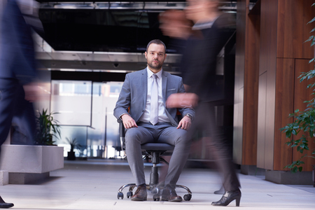 office time: business man sitting in office chair,  people group  passing by: Concept of time, rush, organization