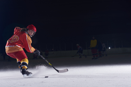 teen girl children ice hockey player in action kicking puck with stick
