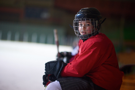 hockey rink: children ice hockey players,  group of people,  team friends waiting and relaxing on bench to start  game