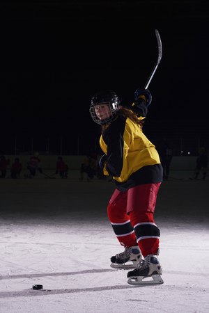 girl action: teen girl children ice hockey player in action kicking puck with stick