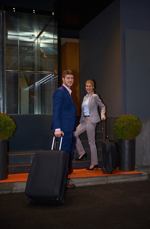 city hotel: Young business people couple entering city  hotel, looking for room, holding suitcases while walking on street Stock Photo
