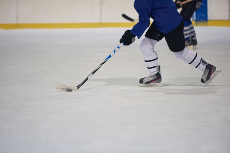 hockey games: ice hockey player in action kicking with stick