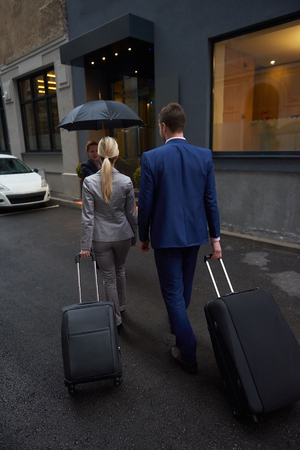 luggage travel: Young business people couple entering city  hotel, looking for room, holding suitcases while walking on street Stock Photo
