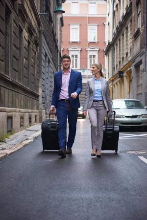 valise voyage: Les jeunes gens d'affaires Couple entrant hôtel de ville, à la recherche de chambre, tenant valises tout en marchant dans la rue