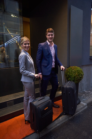 baggage: Young business people couple entering city  hotel, looking for room, holding suitcases while walking on street Stock Photo