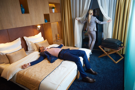 man in suit: relaxed and happy young couple in modern hotel room