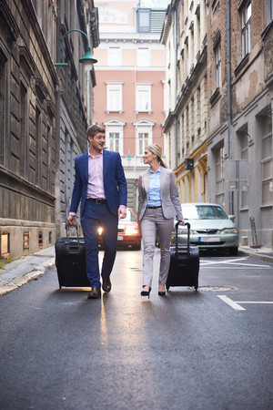 arrival: Young business people couple entering city  hotel, looking for room, holding suitcases while walking on street Stock Photo