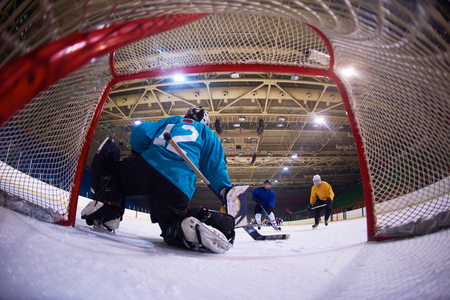 ice arena: ice hockey goalkeeper  player on goal in action
