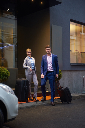 business lounge: Young business people couple entering city  hotel, looking for room, holding suitcases while walking on street Stock Photo