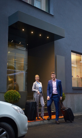 street people: Young business people couple entering city  hotel, looking for room, holding suitcases while walking on street Stock Photo