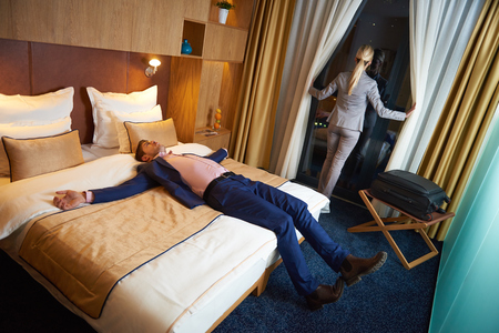 romance bed: relaxed and happy young couple in modern hotel room
