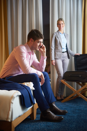 woman laying: relaxed and happy young couple in modern hotel room