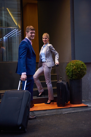 corporate travel: Young business people couple entering city  hotel, looking for room, holding suitcases while walking on street Stock Photo