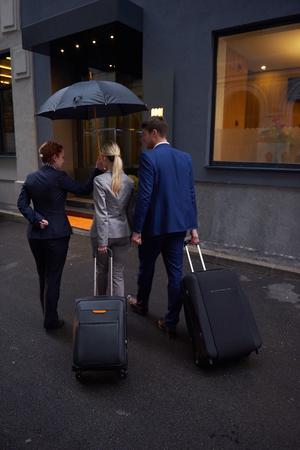 personas en la calle: Los jóvenes empresarios par que entran hotel urbano, en busca de la habitación, que llevan a cabo las maletas mientras camina en la calle