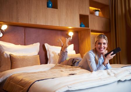 junge Business-Frau im Hotelzimmer entspannen und tv suchen Lizenzfreie Bilder