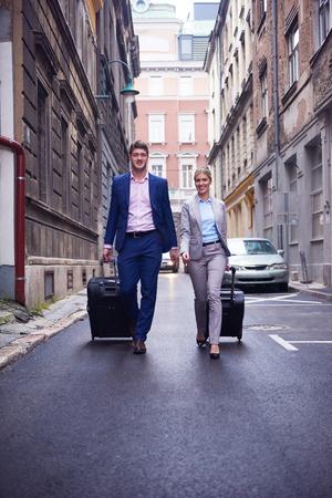 pareja enamorada: Los j�venes empresarios par que entran hotel urbano, en busca de la habitaci�n, que llevan a cabo las maletas mientras camina en la calle