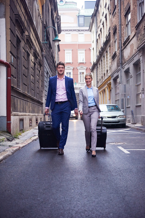 street love: Young business people couple entering city  hotel, looking for room, holding suitcases while walking on street Stock Photo