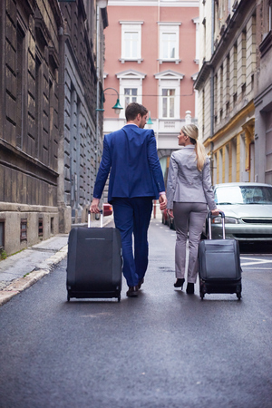 guests: Young business people couple entering city  hotel, looking for room, holding suitcases while walking on street Stock Photo