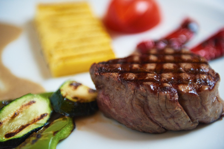 fillets: tasty bbq meat food, juicy beef steak with grilled cheese and salad in restaurant