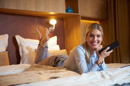 hotel room: young business woman relaxing in hotel room and looking tv