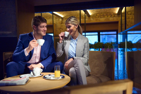 couple talking: young business people couple relaxing after work in bar restaurant and take drink