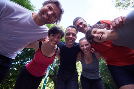 outdoor training: jogging people group, friends have fun,  hug and stack hands together after training
