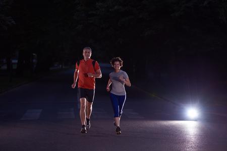 gente corriendo: deportes urbanos, trotar pareja sana en la ciudad en la madrugada en la noche Foto de archivo