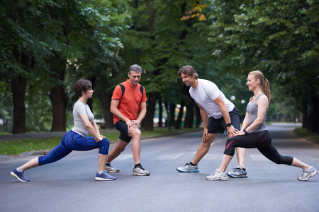 outdoor exercise: jogging people group stretching in park before training