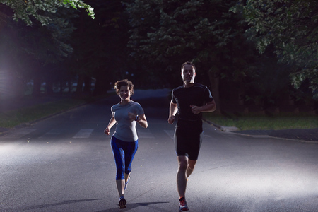 nighttime: urban sports, healthy couple jogging in the city at early morning in night Stock Photo