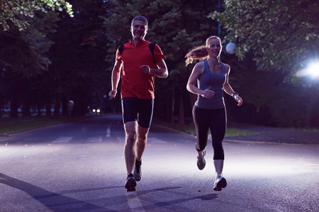 run: urban sports, healthy couple jogging in the city at early morning in night Stock Photo