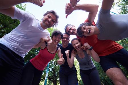 友人は抱擁し、トレーニング後の手を一緒にスタックは楽しい時を過す人グループをジョギング 写真素材