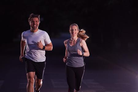 correr: deportes urbanos, trotar pareja sana en la ciudad en la madrugada en la noche Foto de archivo