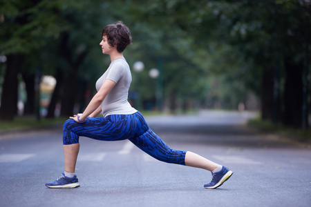 girl legs: runner   woman warming up and stretching before morning jogging