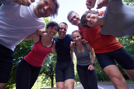 outdoor exercise: jogging people group, friends have fun,  hug and stack hands together after training