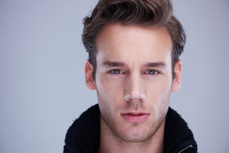 visage homme: beau jeune homme isolé portrait sur fond blanc en studio Banque d'images