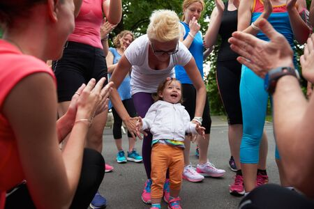 gir: jogging people group, friends have fun with cute little baby gir,  hug and stack hands together after training