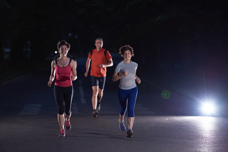 gente corriendo: grupo de personas a correr por la noche, los corredores del equipo en el entrenamiento de la mañana